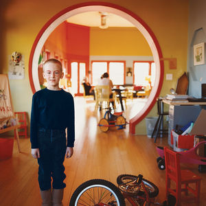 a child with a painted face stands in front of a circular doorway beside a bicycle