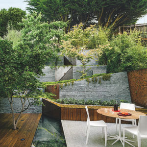 a maple tree grows through an pie deck on a white granite patio
