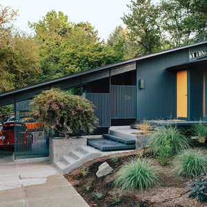 Midcentury house in Portland with iron colored facade and gold front door