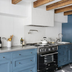 Kitchen with exposed timbers and Wood Mode cabinets in Brooklyn renovation by Elizabeth Roberts.