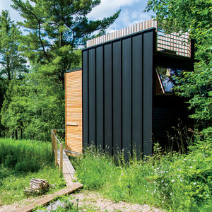 Steel cladding and outdoor fire pit of Wisconsin cabin by Revelations Architects/Builders.