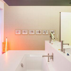 Corian sinks, Ritmonio fixtures, and glowing artwork in bathroom.