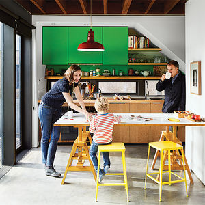 Bright kitchen with green cabinets and an Achille Castiglioni table