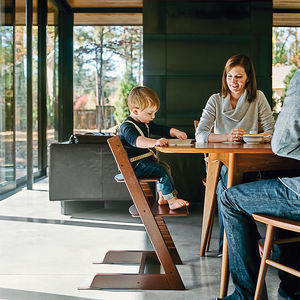 Modern home in North Carolina with newport furniture thatcher chairs, room & board dining table, Stokke high chair and waxed concrete floors in the dining room